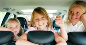 Three young girls in the back of an SUV